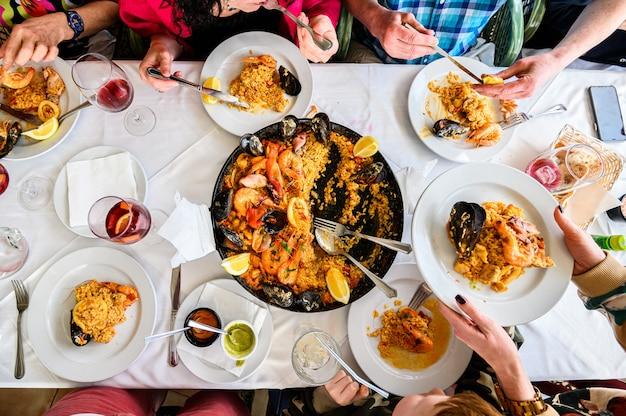 Столик в ресторане с испанской паэлью с морепродуктами подается на сковороде. свежие креветки, креветки с чесночным соусом, мидии, кальмары, осьминоги и морские гребешки. вид сверху. ресторан