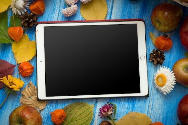 タブレット。秋の明るい背景。花、葉、青い木製の背景に果物。秋の休日と感謝祭の背景。