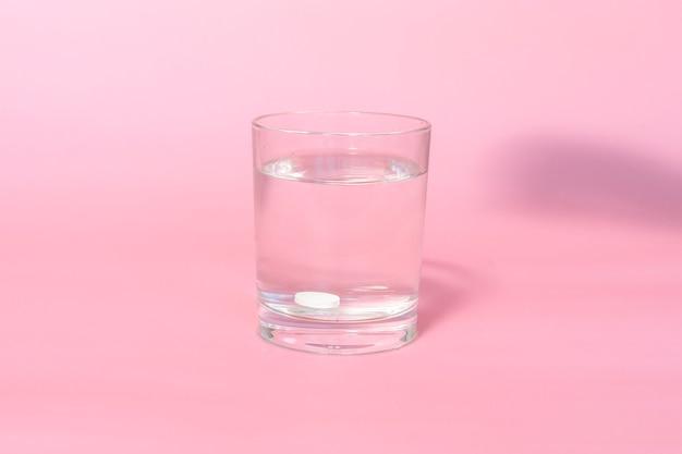 タブレットはピンクの背景にコップ1杯の水に溶けます