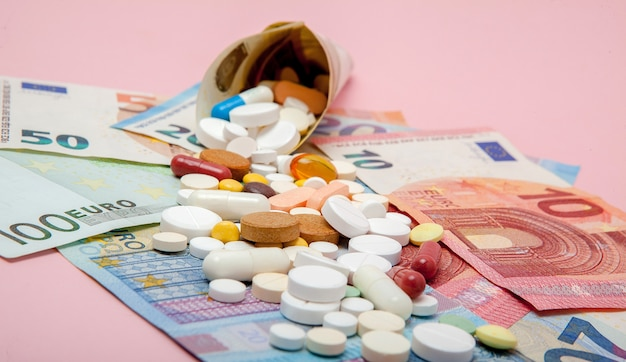 Таблетки, завернутые в евро с банкнотами евро на розовой стене. медицинская концепция
