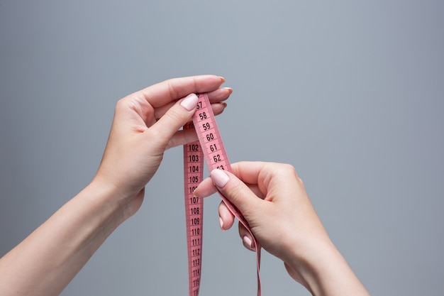 灰色の空間に女性の手でテープ。減量、ダイエット