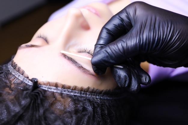Мастер-татуировщик накладывает повторную анестезию на бровь клиента деревянной палочкой, на которую наматывается вата.
