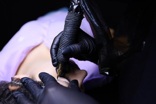 Художник-татуировщик в черных перчатках одной рукой вытянул бровь клиента, другой рукой держит машинку и наносит татуировку.