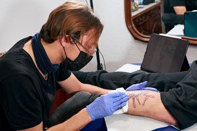 男の足に新しく完成したタトゥーを掃除する青い手袋をしたタトゥー アーティスト