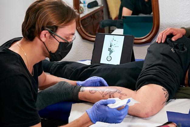 남자 다리에 새로 완성 된 문신을 청소하는 파란색 장갑을 착용 한 문신 아티스트