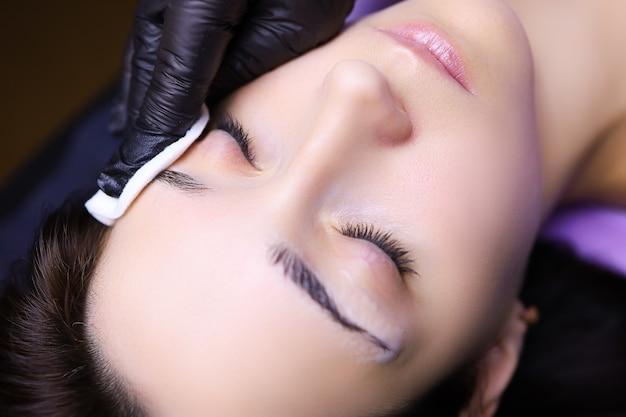 Тату мастер подготавливает брови клиента к процедуре перманентного макияжа протирает ватной губкой.