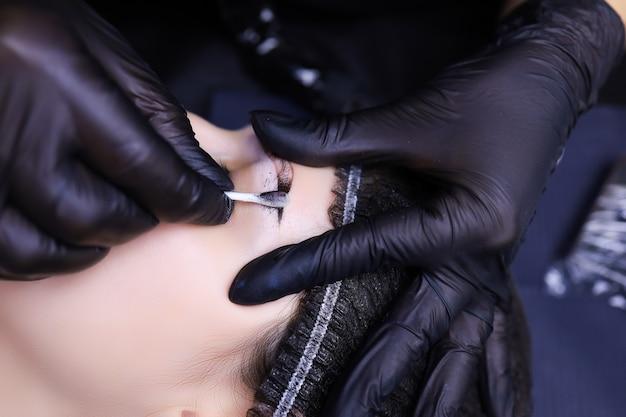 タトゥーアーティストの手は、片方の手でクライアントの眉毛を持ち、もう一方の手で綿棒を持って残りの色素を拭き取り、閉じます。