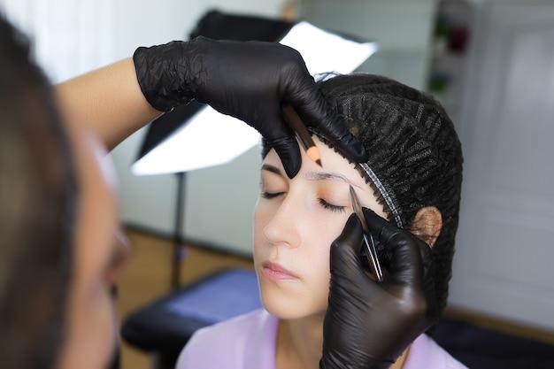 Художник-татуировщик стоит перед клиентом, держа бровь и считая волосы пинцетом.