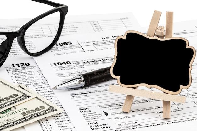 Налоговые бланки с деньгами, ручкой и доской с местом для текста.