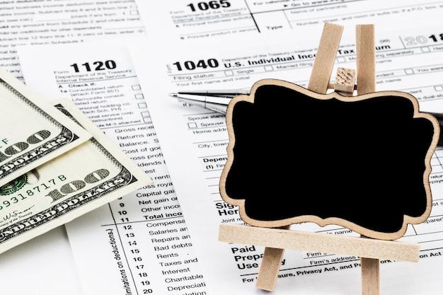 納税申告書には、お金、ペン、黒板にテキスト用のスペースがあります。