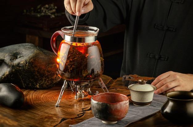 Чайная церемония заваривания чая на огне в стеклянном чайнике