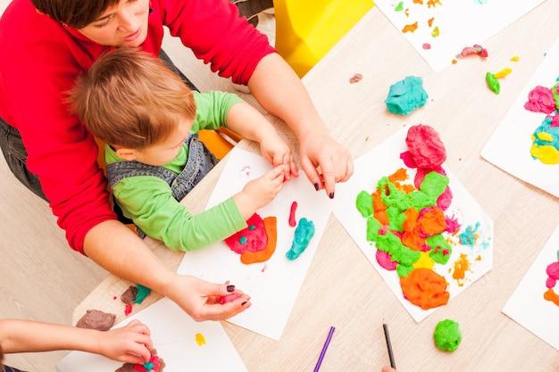 교사는 소년이 테이블에 그림 플라스틱을 만드는 것을 돕습니다.