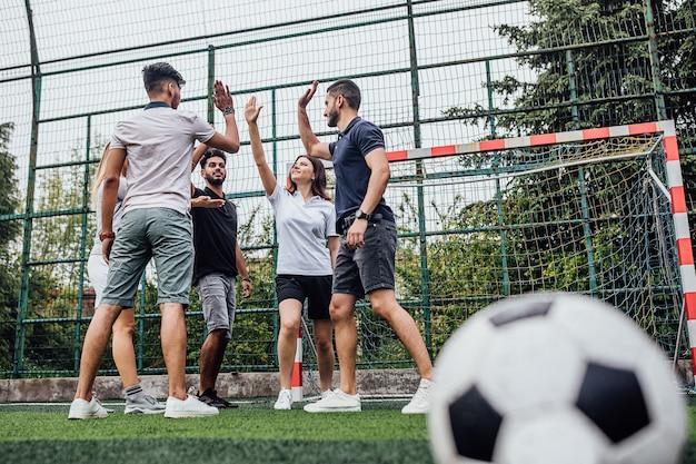 勝者として立って叫んでいるサッカーユニフォームのチームは、良い時間を過ごします
