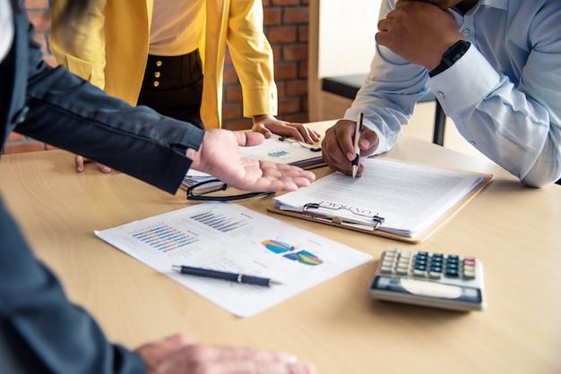 Команда работает над бухгалтерскими документами, а команда работает вместе, чтобы представить работу и помочь решить проблему.