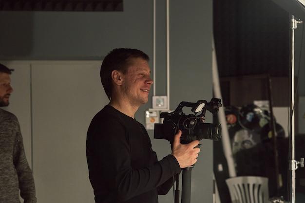 На площадке работает команда режиссера, видеодеоператоров и актеров. видеопродакшн, бэкстейдж, производство видеоконтента.