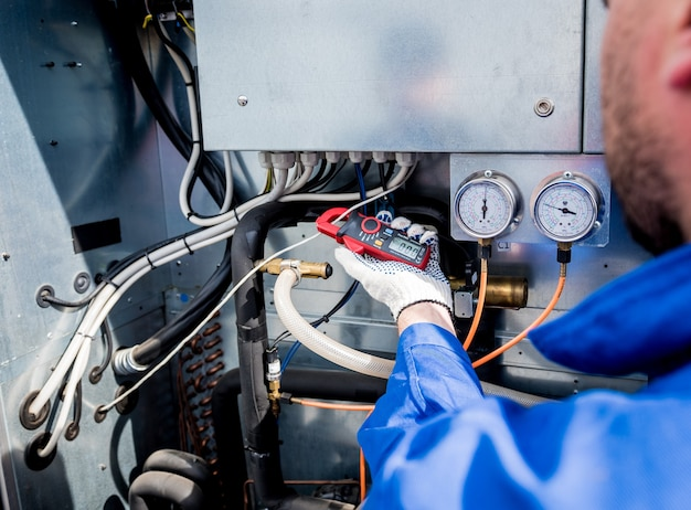 電流クランプで熱交換器の電力線をチェックする技術者
