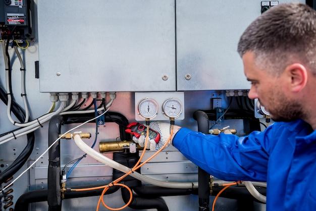 전류 클램프로 열교환 기의 전력선을 확인하는 기술자