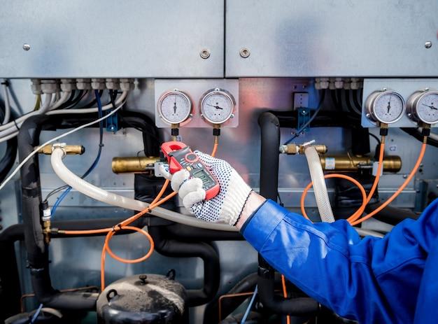 전류 클램프로 열교환기의 전력선을 점검하는 기술자