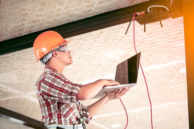 技術者が信号をチェックしています。建物にインターネットを設置した後