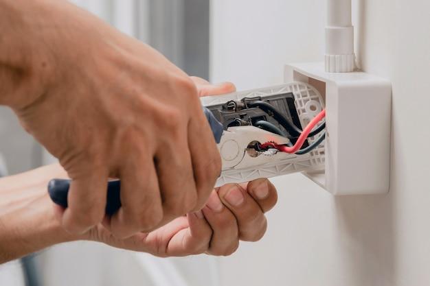 Техник использует плоскогубцы для установки вилки питания на стене.