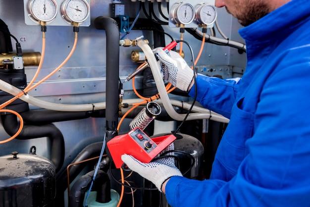 Техник ремонтирует электронные датчики температуры с помощью электронного паяльника.