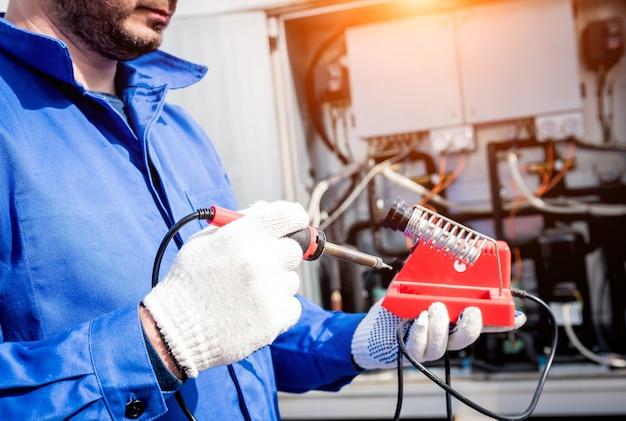 技術者は電子はんだごてで電子温度センサーを修理します