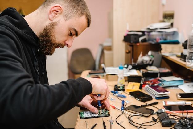 ラボでスマートフォンのマザーボードを修理する技術者。コンピューターハードウェア、携帯電話、電子、修理、アップグレード、技術の概念。ワークショップで電話修理のプロセスを示す男。