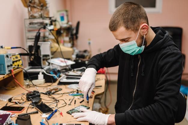 ラボでスマートフォンのマザーボードを修理する技術者。携帯電話、電子、修理、アップグレード、技術の概念。コロナウイルス。男は働いて、ワークショップで防護マスクを着ています。