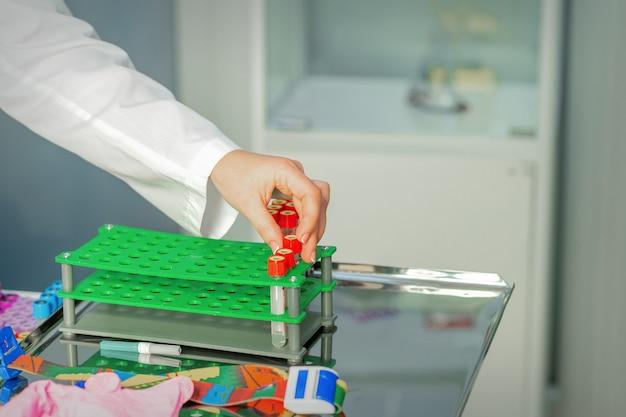 기술자의 손이 빈 혈액 튜브 검사를 실험실의 랙에 넣습니다.