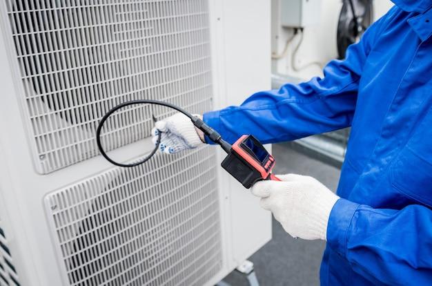Техник использует цифровую камеру, чтобы проверить засорение теплообменника.