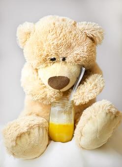 Медвежонок сидит и ест мед