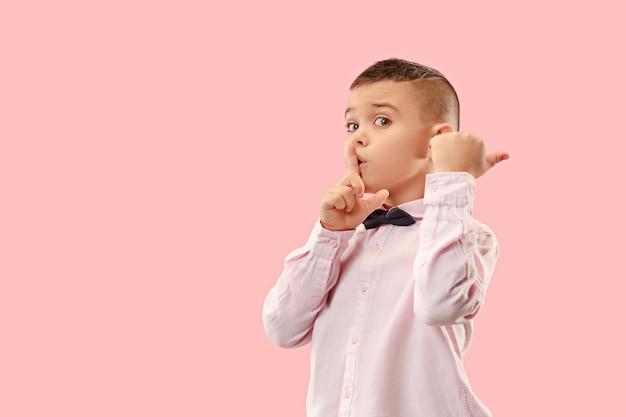 Мальчик-подросток шепчет секрет за ее рукой на розовом фоне