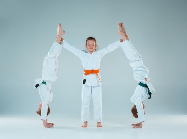 무술 학교에서 합기도 훈련에서 싸우는 십대 소년과 소녀. 건강한 생활 방식과 스포츠 개념입니다. 흰색 배경에 흰색 기모노를 입은 십대들. 집중된 얼굴을 가진 아이들