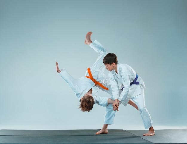 무술 학교에서 합기도 훈련에서 싸우는 십대 소년들. 건강한 생활 방식과 스포츠 개념입니다. 흰색 배경에 흰색 기모노를 입은 십대들. 집중된 얼굴을 가진 아이들