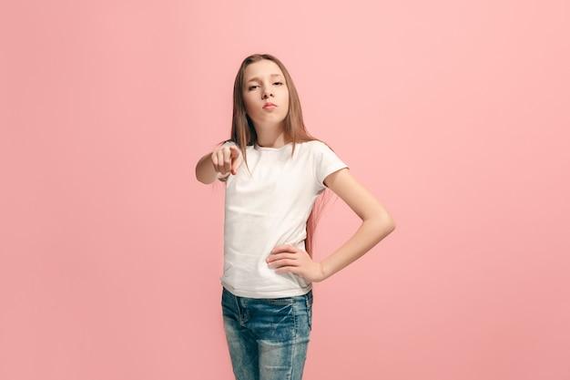 Девушка-подросток, указывая на передний портрет крупным планом на розовой стене