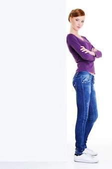 空白の宣伝板の近くに立っている顔に真剣な光景を持つ十代の少女
