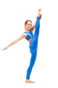Девушка подростка делая тренировки гимнастики изолированные на белизне