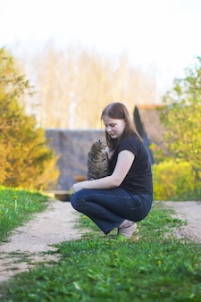 시골의 봄 자연 배경에서 야외에서 사랑스러운 줄무늬 회색 고양이와 노는 십대 소녀.