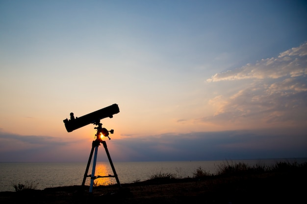 Силуэт телескопа на оранжевом закате