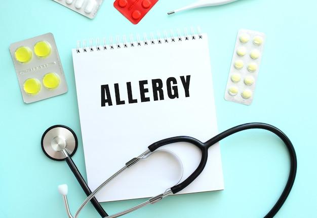 Allergy라는 텍스트는 파란색 배경에 청진기와 알약 옆에 있는 흰색 메모장에 쓰여 있습니다.
