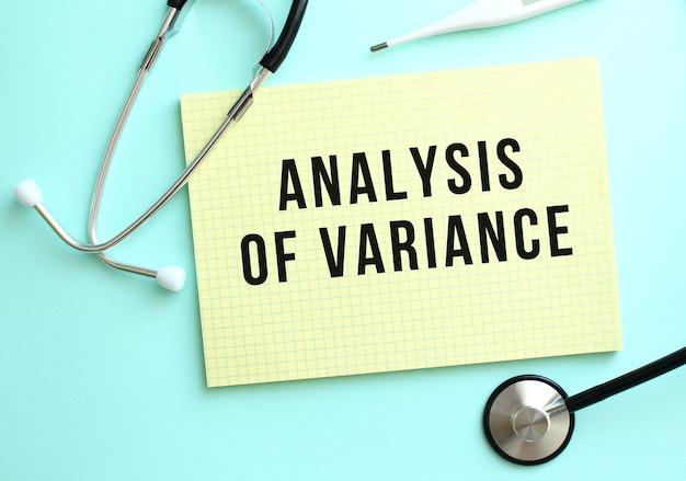 Analysis of variance라는 텍스트는 파란색 배경의 청진기 옆에 있는 노란색 패드에 쓰여 있습니다. 의료 개념