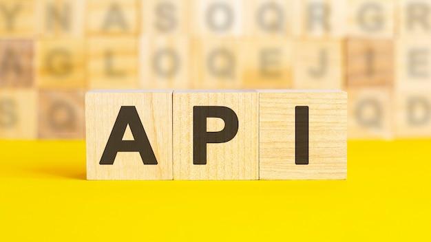 テキストapiは、明るい黄色の表面にある木製の立方体に記述されています。背景には、異なる文字の立方体の行があります。ビジネスコンセプト。 api-アプリケーションプログラミングインターフェイスの略
