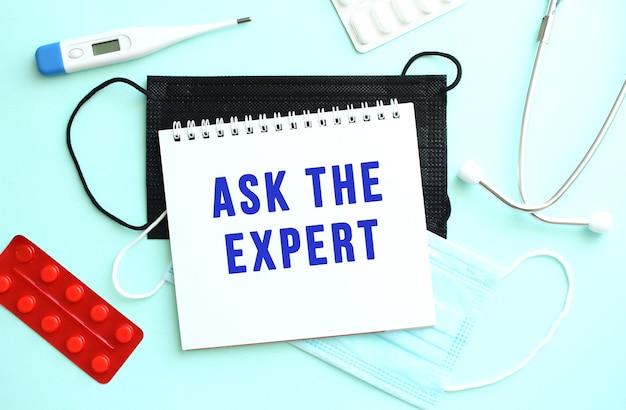 Ask the expert라는 텍스트는 온도계와 의료용 마스크 옆에 있는 파란색 배경에 있는 공책에 기록되어 있습니다.