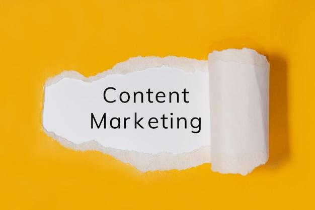 Текст content marketing за рваной желтой бумагой
