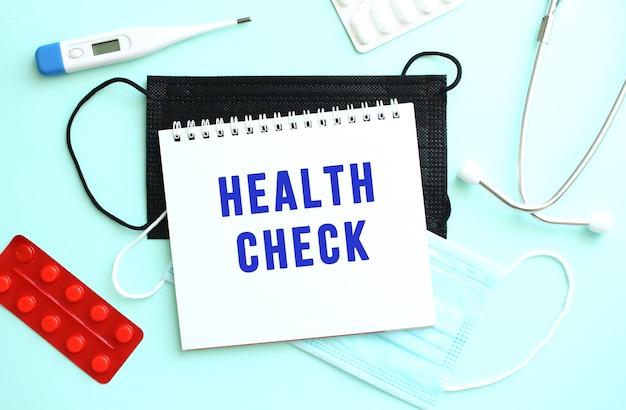 Health check라는 텍스트는 온도계와 의료 마스크 옆에 있는 파란색 배경에 있는 공책에 쓰여 있습니다.