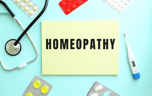 Homeopathy라는 텍스트는 파란색 배경에 약인 청진기 옆에 있는 노란색 공책에 쓰여 있습니다.