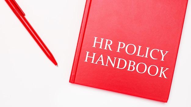 Hr policy handbookというテキストは、オフィスの白いテーブルの赤いペンの近くにある赤いメモ帳に書かれています。ビジネスコンセプト