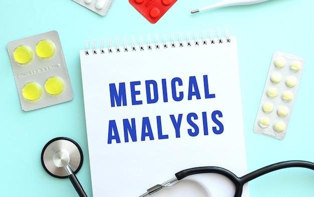 텍스트 의료 분석은 ab의 청진기 약 옆에 있는 노트북에 기록됩니다.