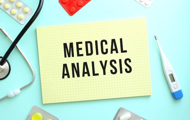 Medical analysis라는 텍스트는 파란색 배경의 청진기 옆에 있는 노란색 공책에 기록됩니다.