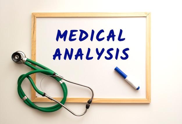 テキストmedicalanalysisは、マーカー付きの白いオフィスボードに書かれています。近くには聴診器があります。医療の概念。